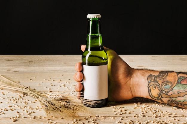 Primo piano della mano di una persona con spighe di grano sulla tavola di legno Foto Gratuite
