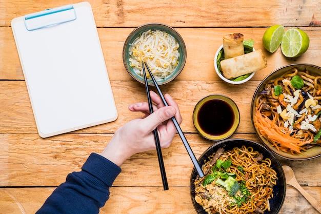Primo piano della mano di una persona raccogliendo germogli di fagioli con le bacchette sul tavolo Foto Gratuite