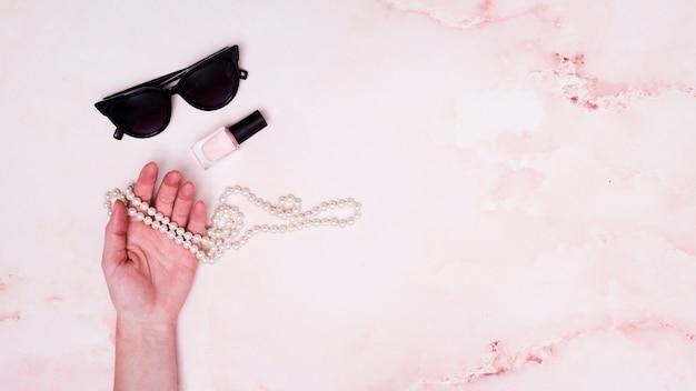 Primo piano della mano femminile che regge la collana di perle; bottiglia di smalto per unghie e occhiali da sole su sfondo rosa Foto Gratuite