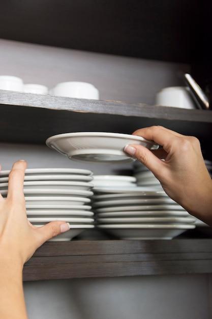 Primo piano della mano impilabile piattino bianco nella mensola Foto Gratuite