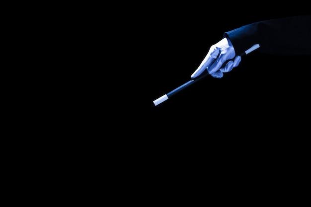 Primo piano della mano magica che tiene la bacchetta magica su sfondo nero Foto Gratuite