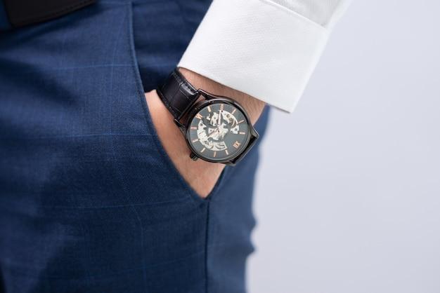 Primo piano della mano maschile in tasca con orologio da polso elegante moderno Foto Gratuite