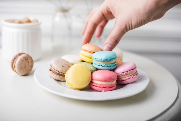Primo piano della mano raccogliendo i maccheroni colorati dal piatto bianco sul tavolo Foto Gratuite