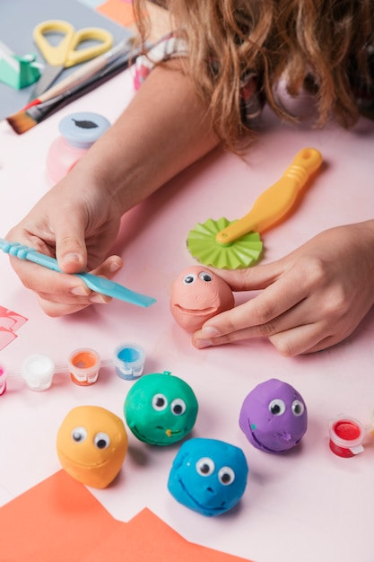 Primo piano della mano umana che fa fronte di argilla colorata Foto Gratuite