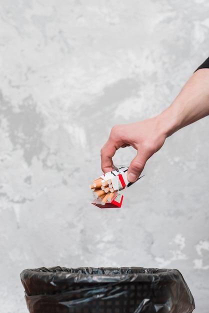 Primo piano della mano umana che getta pacchetto di sigarette Foto Gratuite