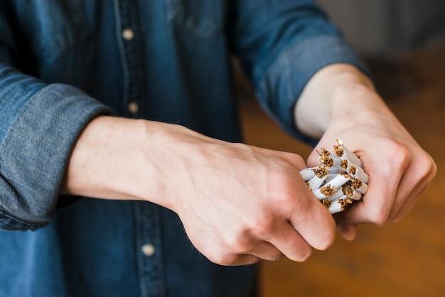 Primo piano della mano umana che rompe il pacco di sigarette Foto Gratuite