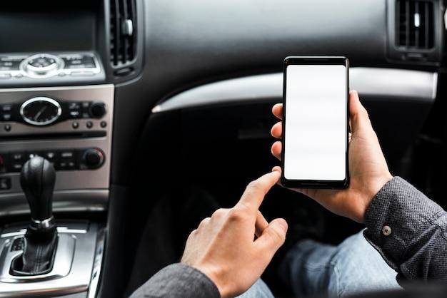 Primo piano della mano utilizzando smartphone con display bianco seduto in macchina Foto Gratuite