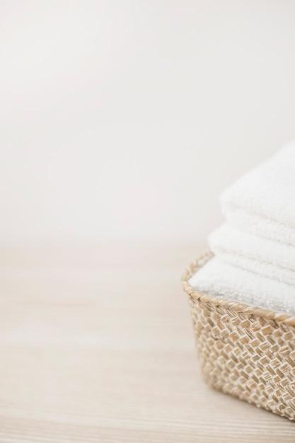 Primo piano della merce nel carrello bianca degli asciugamani sul ripiano del tavolo di legno Foto Gratuite