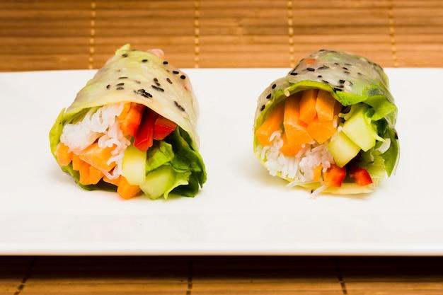 Primo piano della molla di riso e dei semi di sesamo saporiti della verdura sul piatto Foto Gratuite