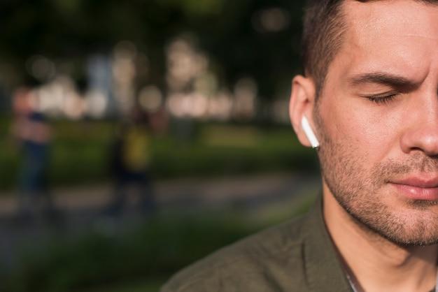 Primo piano della musica d'ascolto dell'uomo con il trasduttore auricolare senza fili Foto Gratuite
