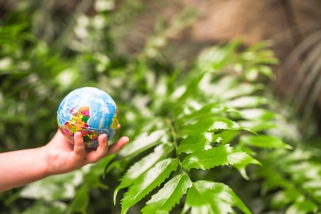 Primo piano della palla del globo della tenuta della mano del bambino davanti alla pianta Foto Gratuite
