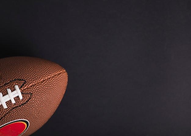 Primo piano della palla di rugby marrone su sfondo nero Foto Gratuite