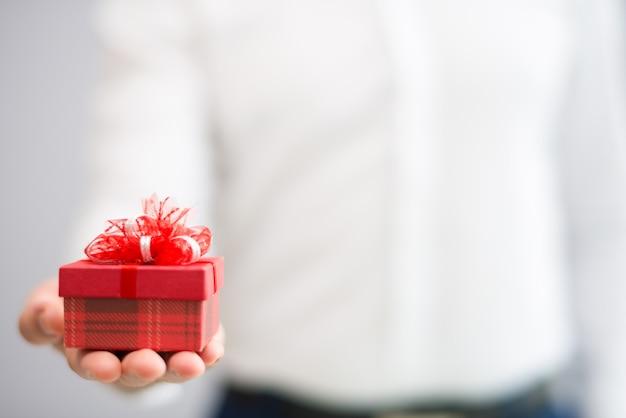 Primo piano della persona che dà il piccolo contenitore di regalo rosso con l'arco Foto Gratuite