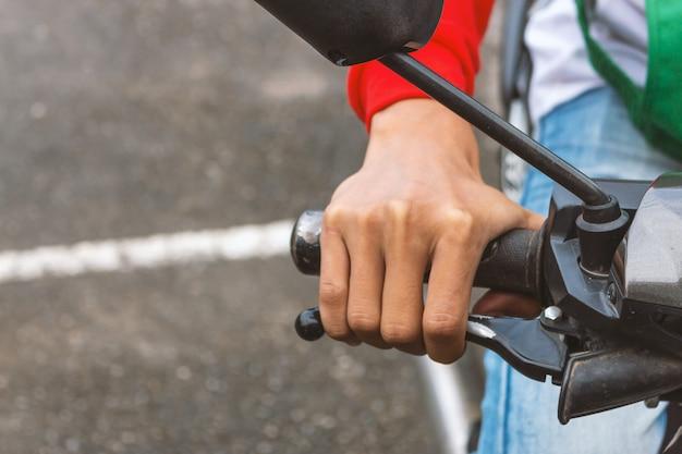 Primo piano della persona che tiene il manubrio della moto Foto Premium