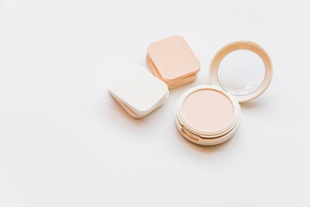 Primo piano della polvere compatta di plastica realistica cosmetica con le spugne sul contesto bianco Foto Gratuite