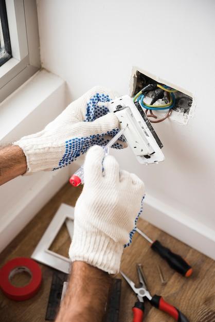 Primo piano della presa della spina della riparazione della mano dell'elettricista sulla parete bianca a casa Foto Gratuite