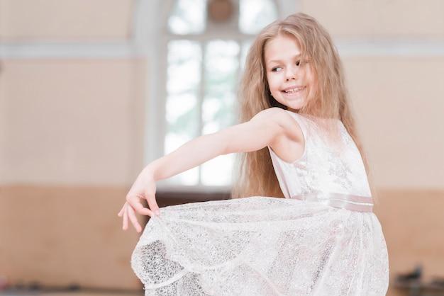 Primo piano della ragazza della ballerina che tiene il suo vestito Foto Gratuite