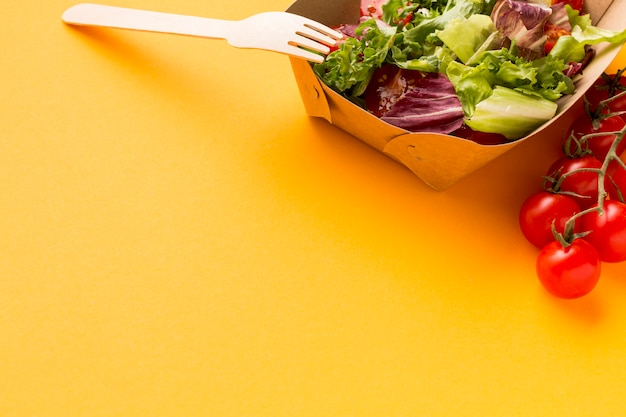 Primo piano della scatola di insalata deliziosa con i pomodori Foto Gratuite