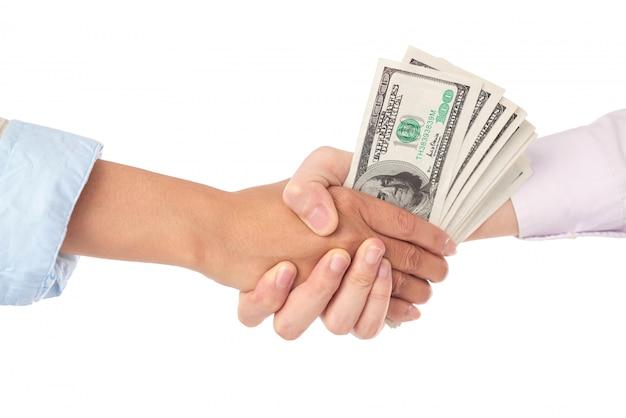 Primo piano della stretta di mano con le banconote in dollari nel mezzo Foto Gratuite