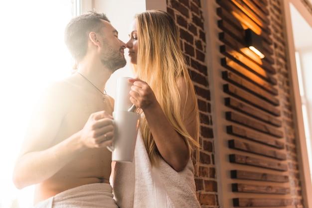 Primo piano della tazza da caffè della tenuta delle giovani coppie che si bacia Foto Gratuite