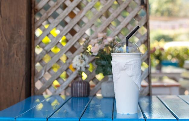 Primo piano della tazza di bevanda sulla tabella pranzante blu impostata in corte dell'alimento Foto Premium