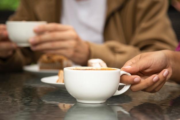 Primo piano della tazza di caffè della tenuta della donna Foto Gratuite