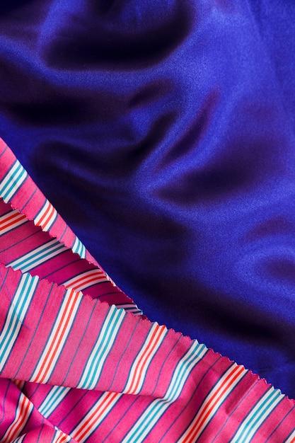Primo piano della tessile del reticolo delle bande sul panno blu liscio Foto Gratuite