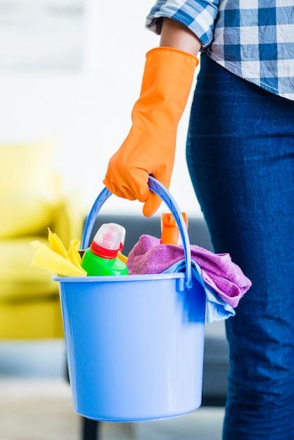 Primo piano delle attrezzature femminili di pulizia della tenuta del portiere nel secchio blu Foto Gratuite