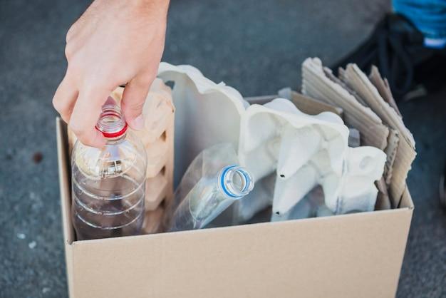 Primo piano delle bottiglie di plastica e del cartone dell'uovo nella scatola Foto Gratuite