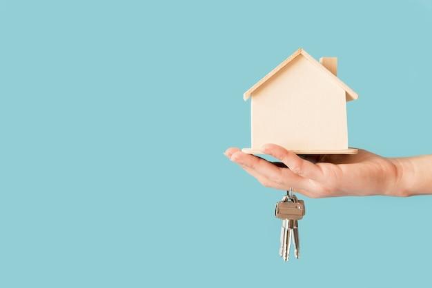 Primo piano delle chiavi della tenuta della mano e del modello di legno della casa contro fondo blu Foto Gratuite