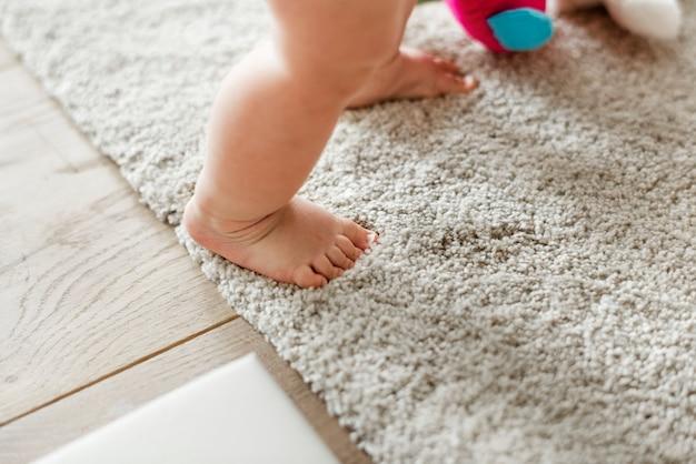 Primo piano delle gambe del bambino mentre levandosi in piedi Foto Gratuite