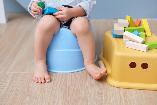 Primo piano delle gambe di piccola seduta asiatica sveglia del bambino del neonato di 18 mesi del bambino Foto Premium