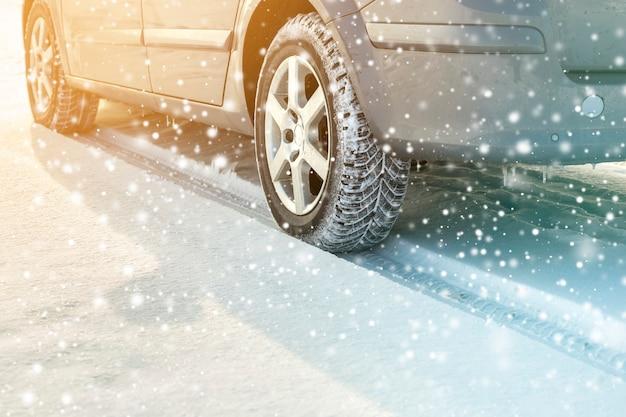 Primo piano delle gomme di gomma delle ruote di automobile nella neve profonda di inverno. concetto di trasporto e sicurezza. Foto Premium
