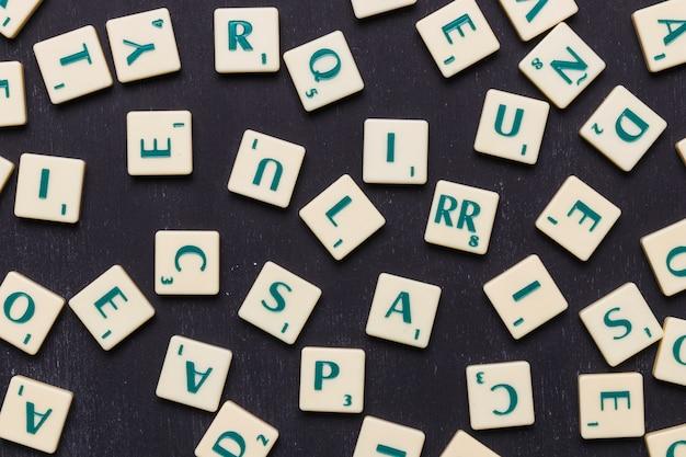 Primo piano delle lettere di scrabble contro fondo nero Foto Gratuite