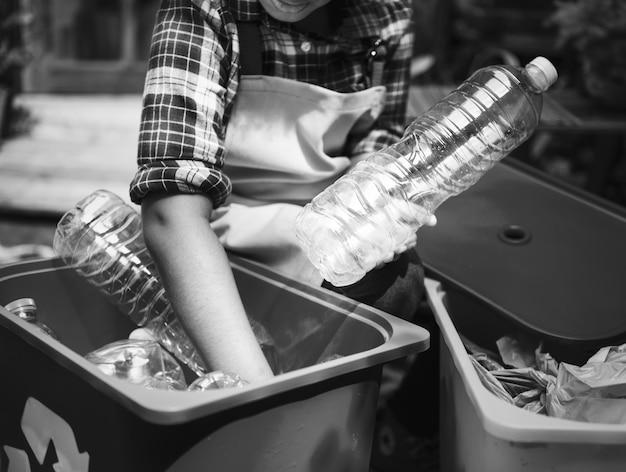 Primo piano delle mani che separano le bottiglie di plastica Foto Gratuite