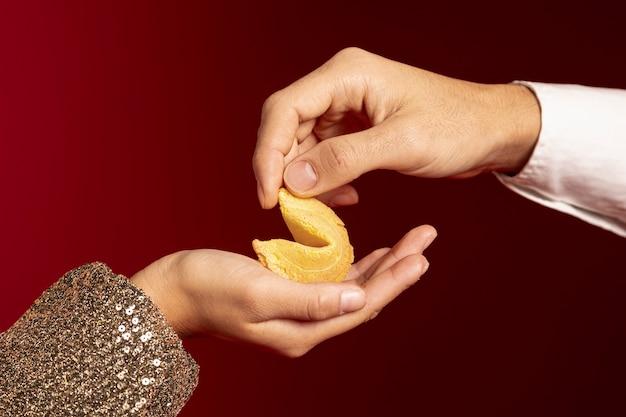 Primo piano delle mani che tengono il biscotto di fortuna per il nuovo anno cinese Foto Gratuite