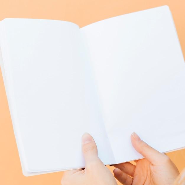 Primo piano delle mani che tengono il libro bianco in bianco contro il contesto colorato Foto Gratuite