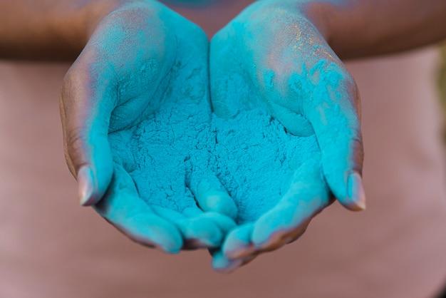 Primo piano delle mani che tengono polvere blu Foto Gratuite