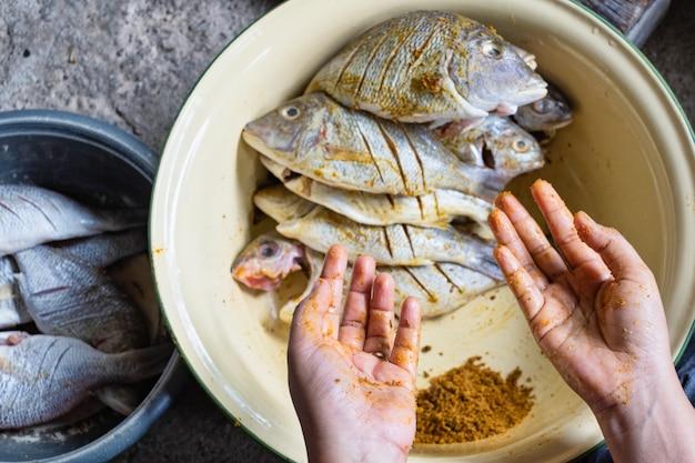 Primo piano delle mani con polvere di curcuma bagnata con pesce crudo. messa a fuoco selettiva. Foto Premium