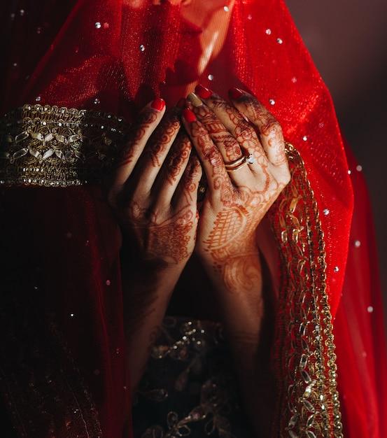 Primo piano delle mani della sposa indù coperto con tatuaggi all'hennè Foto Gratuite