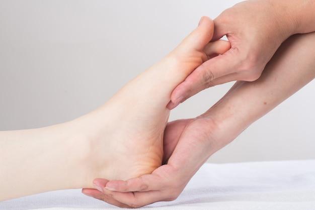 Primo piano delle mani femminili che fanno massaggio ai piedi Foto Premium