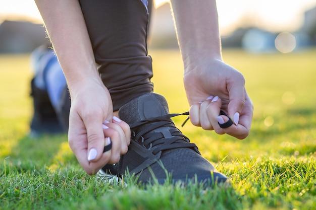 Primo piano delle mani femminili che legano laccetto sulle scarpe da corsa prima della pratica. runner si prepara per l'allenamento. sport stile di vita attivo. Foto Premium