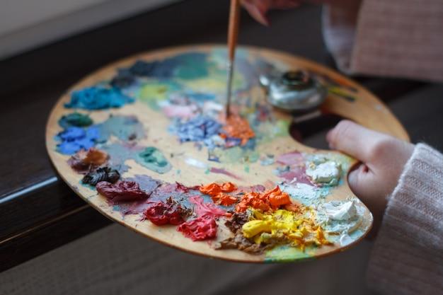 Primo piano delle mani femminili che mescolano le vernici su una gamma di colori con una spatola che crea una pittura a olio Foto Premium
