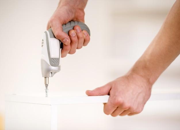 Primo piano delle mani maschili con trapano. Foto Premium