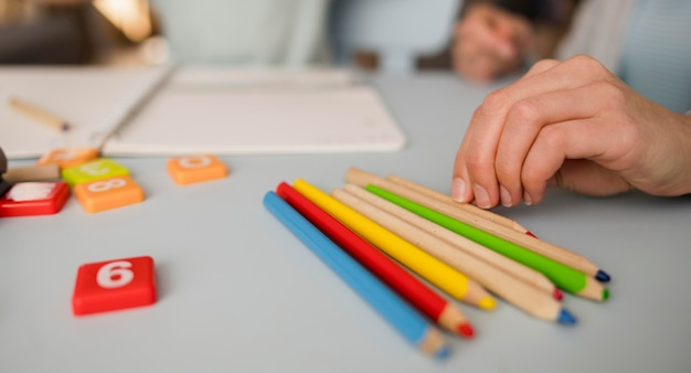 Primo piano delle matite sulla tavola durante la sessione di insegnamento a casa Foto Gratuite