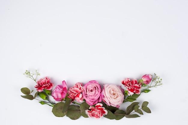 Primo piano delle rose dentellare e dei fiori rossi del garofano contro priorità bassa bianca Foto Gratuite