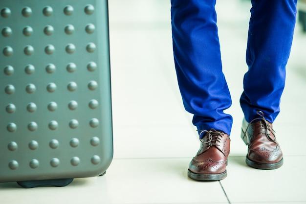 Primo piano delle scarpe e dei bagagli degli uomini all'aeroporto. giovane uomo turistico all'aeroporto pronto per viaggiare Foto Premium