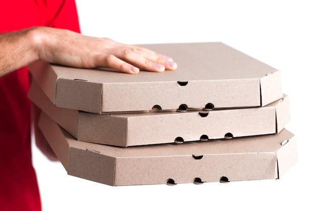 Primo piano delle scatole della tenuta del ragazzo della pizza di consegna Foto Gratuite
