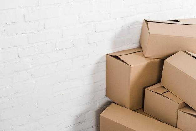 Primo piano delle scatole di cartone davanti al muro di mattoni bianco Foto Gratuite