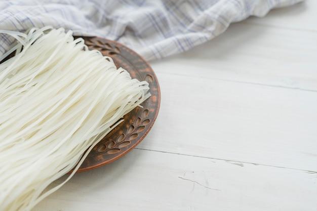 Primo piano delle tagliatelle dei vermicelli del riso sul piatto rotondo con la tovaglia sopra fondo bianco Foto Gratuite